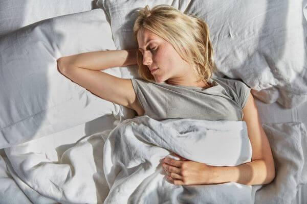 blonde woman in grey t-shirt sleeping under white duvet cover